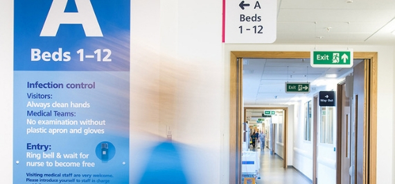 Photo shows part of an empty ward with signs against the wall and a long corridor