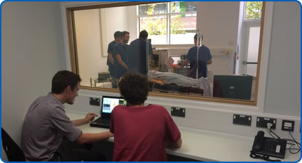 Trainers watch clinicians carrying out a scenario using a manikin in the Sim Space at Southmead Hospital