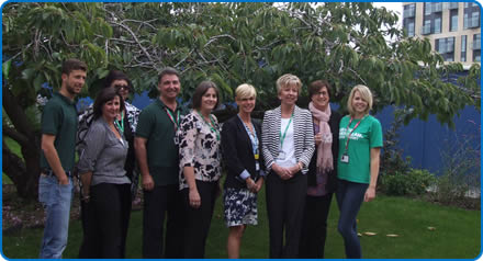 Staff, volunteers and Macmillan representatives celebrate at  NGS Macmillan Wellbeing Centre